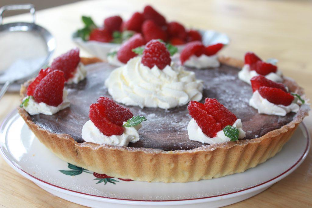 Dark chocolate tart with cream and strawberries