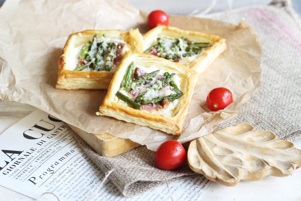 Tartellette agli asparagi con prosciutto e formaggio spalmabile su tagliere