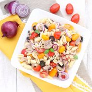 Pasta salad with tuna chunks, onion and baby plum tomatoes