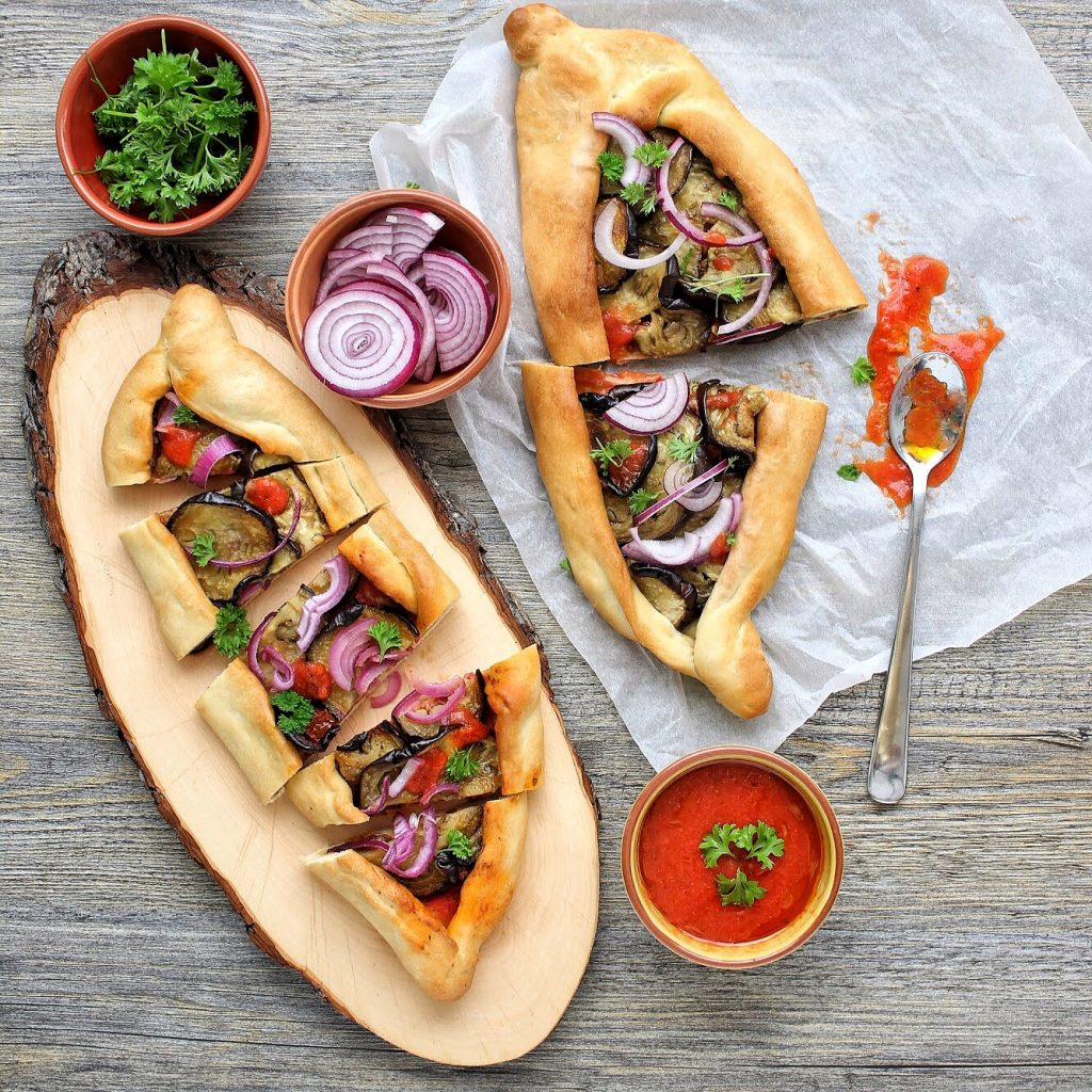 Aubergine pizza pide with onion and tomato sauce - flatlay