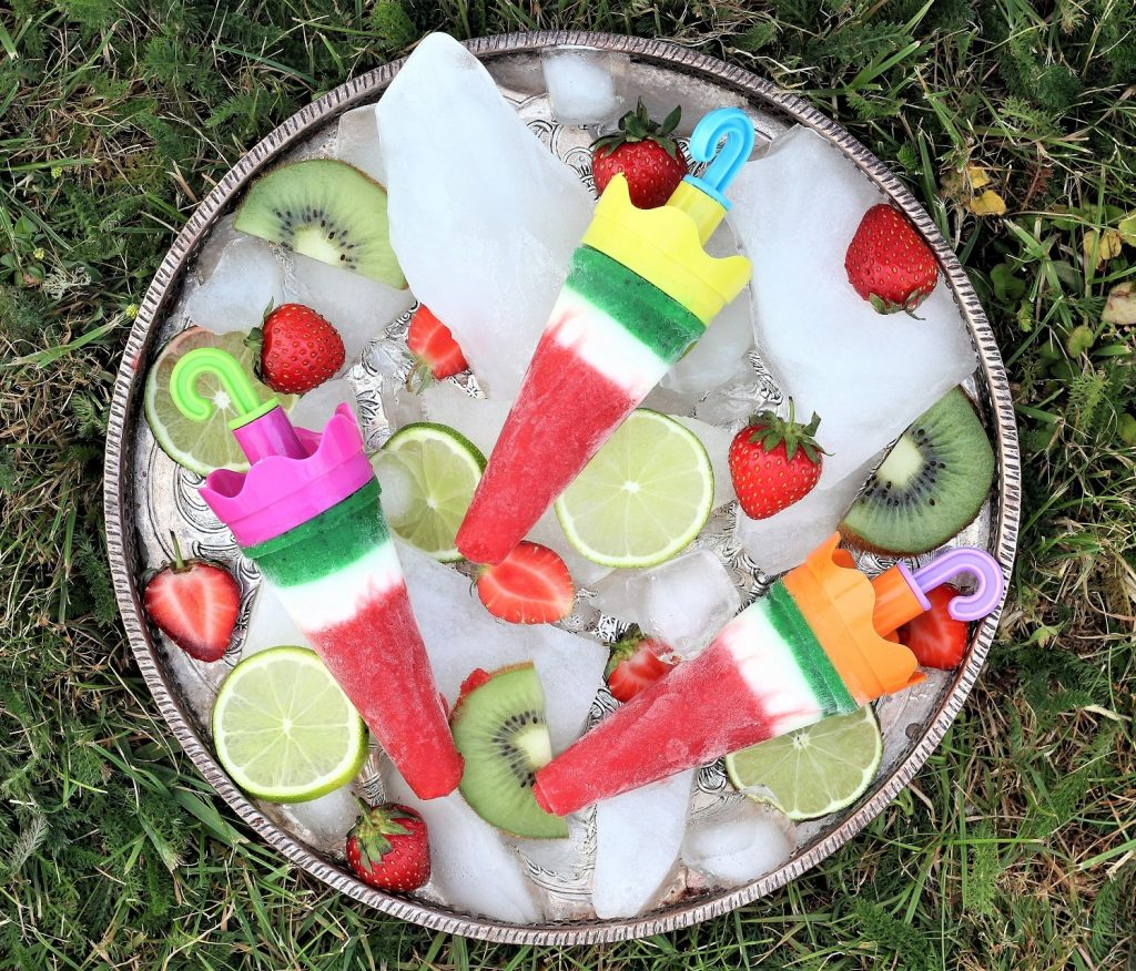 Ice lollies with yogurt, strawberry and kiwi on the tray