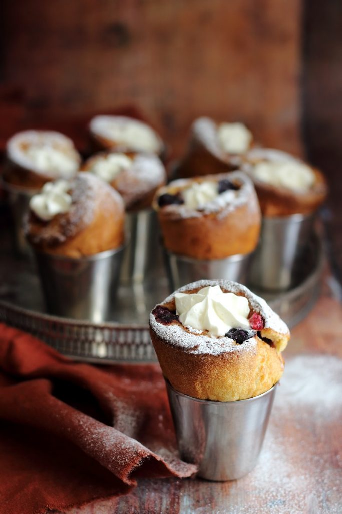 Blueberry and raspberry popovers with cream and icing sugar