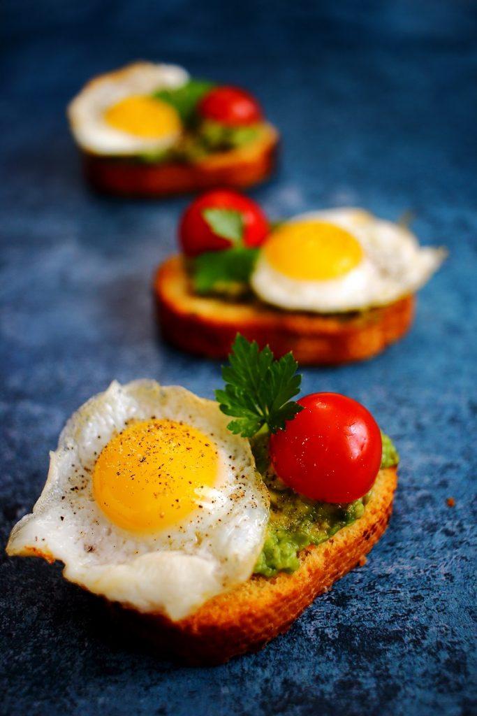 Crostini con avocado, uova di quaglia al tegamino e pomodoro